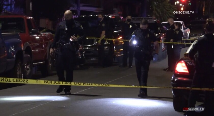 Officers search for evidence following a shooting Friday night on Trojan Avenue in City Heights.