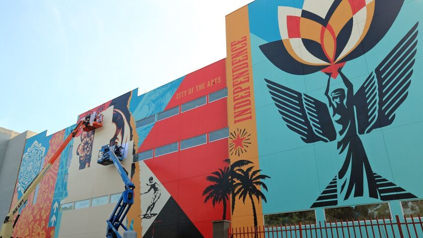 Team members of street artist Shepard Fairey work on completing a massive mural on the Westside of B