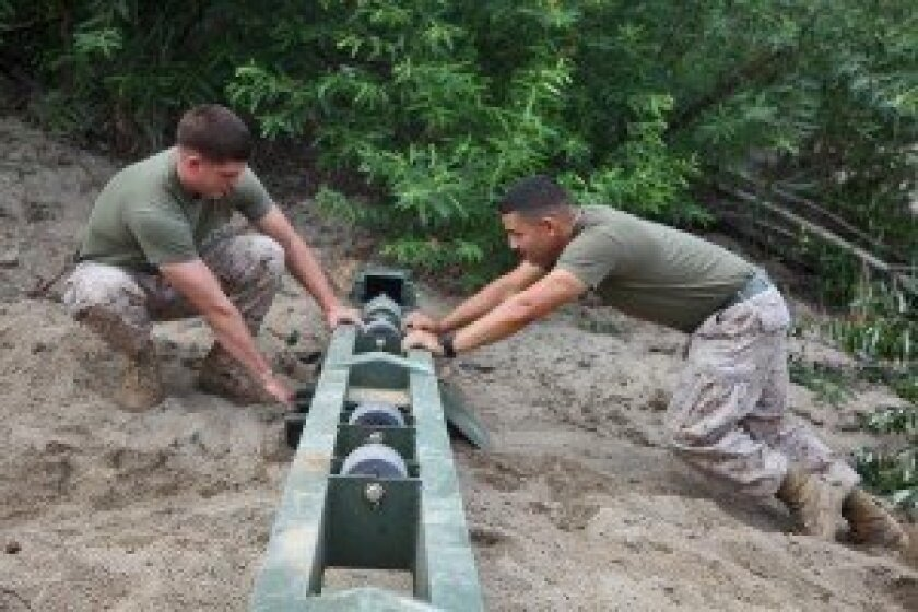 Hettrick, left, works with Lance Cpl. Christopher De Casanova, combat engineer, to move a roller beam that will support a bridge for the Camp Pendleton Mud Run. Photo by Lance Cpl. Keenan Zelazoski.