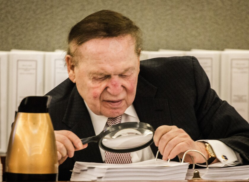 Sheldon Adelson, the billionaire casino developer, reads a deposition in April in a wrongful termination case. Adelson has shown a willingness to spend freely on the candidate of his choosing, and GOP hopefuls are lining up for his support.