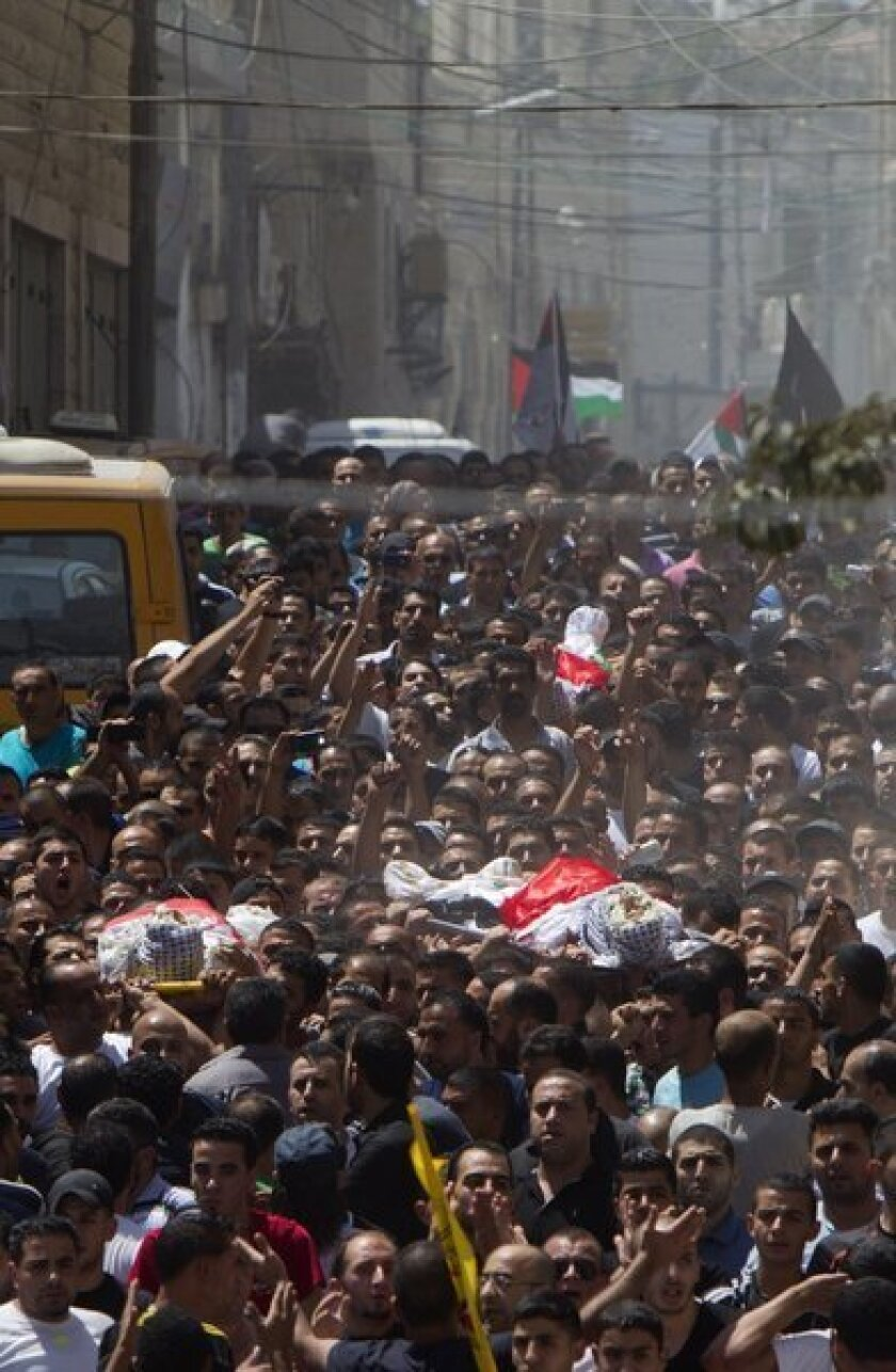 Palestinian mourners carry the bodies of three men who were killed during clashes with Israeli security forces in the West Bank's Kalandia refugee camp on Monday.