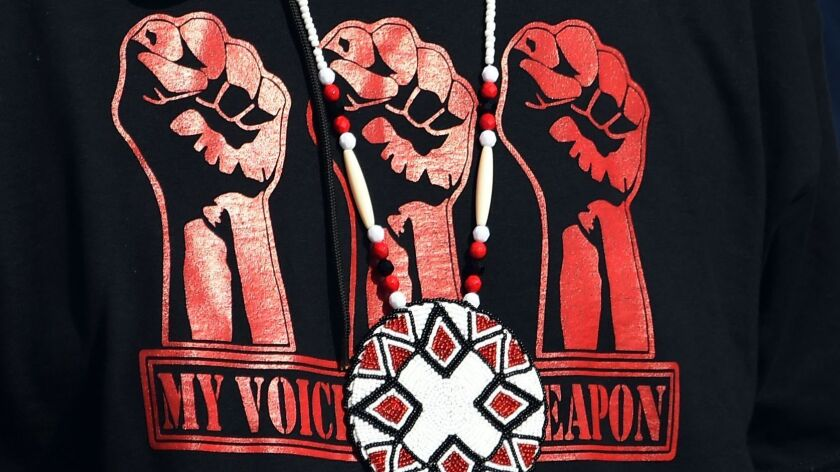 """A Native American protester's shirt reads, """"My voice is my weapon."""""""
