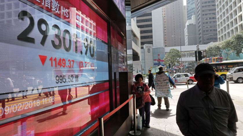 A man walks past an electronic board showing Hong Kong share index outside a local bank in Hong Kong