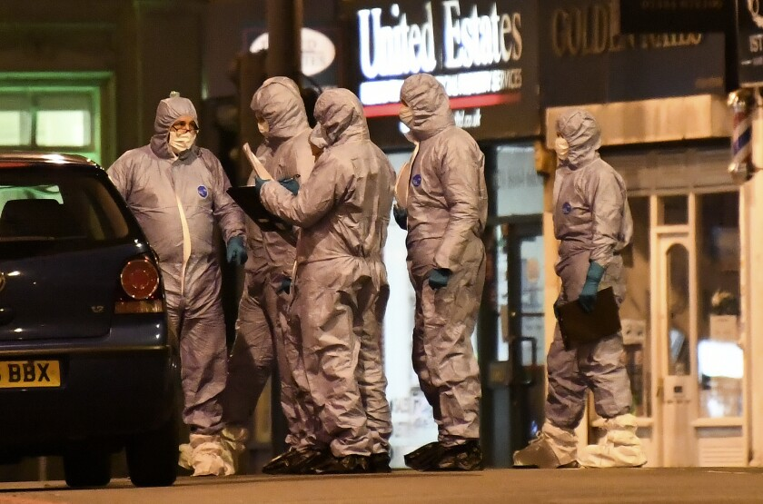 Police forensic officers work near the scene after a stabbing incident in Streatham London, England, Sunday, Feb. 2, 2020. London police officers shot and killed a suspect after at least two people were stabbed Sunday in what authorities are investigating as a terror attack.