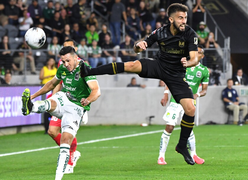Leon's Ramiro Gonzalez, left, kicks the ball away as LAFC's Diego Rossi tries to block it in the first half during the CONCACAF Champions League match at Banc of California on Thursday.