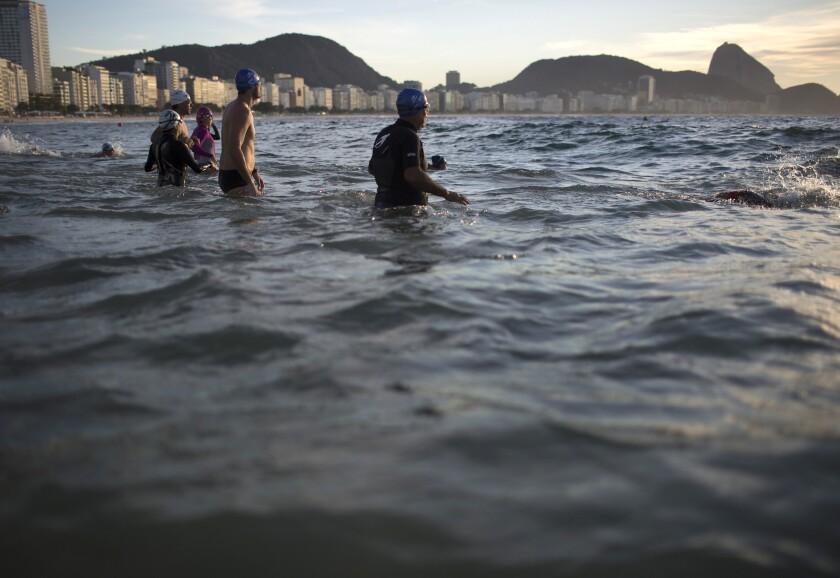 Personas entran al agua en la playa de Copacabana el 14 de julio de 2015 en Río de Janeiro, Brasil. (AP Photo/Leo Correa)