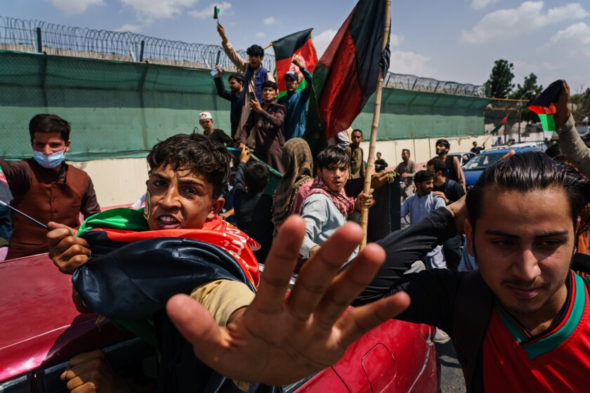 People march in the street carrying red, green and black Afghan flags.