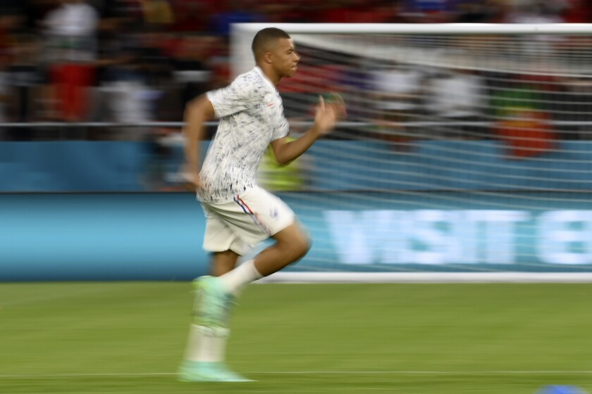 France's Kylian Mbappe runs during warmup before the Euro 2020 soccer championship group F match between Portugal and France at the Puskas Arena in Budapest, Wednesday, June 23, 2021. (Franck Fife, Pool photo via AP)