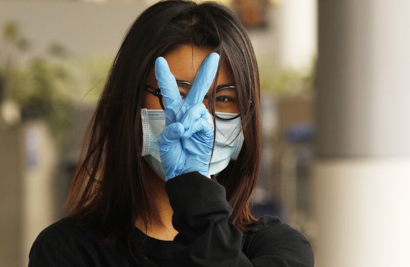 Yiran Zou, a student at the California College of Art in San Francisco, prepares to fly home to China from Los Angeles International Airport, where all travelers must wear face coverings.