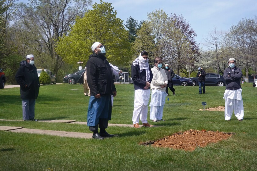 Mourners pray at a grave in in Elgin, Illinois, in 2020.