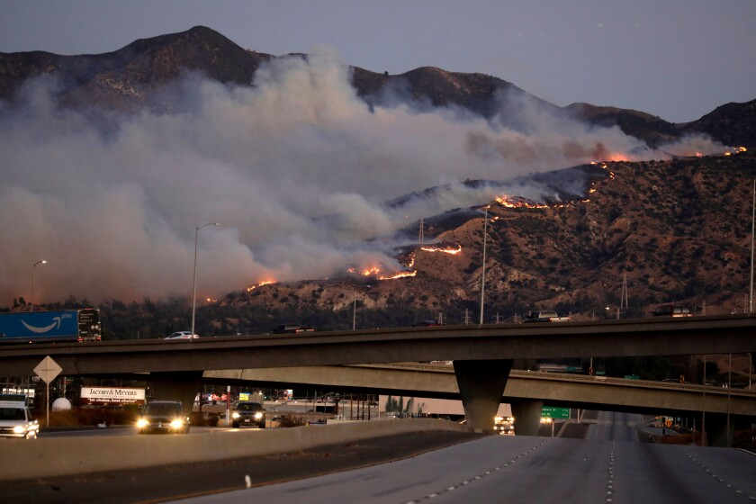Flames and thick clouds of smoke in the hills can be seen from a freeway in the Saddleridge fire