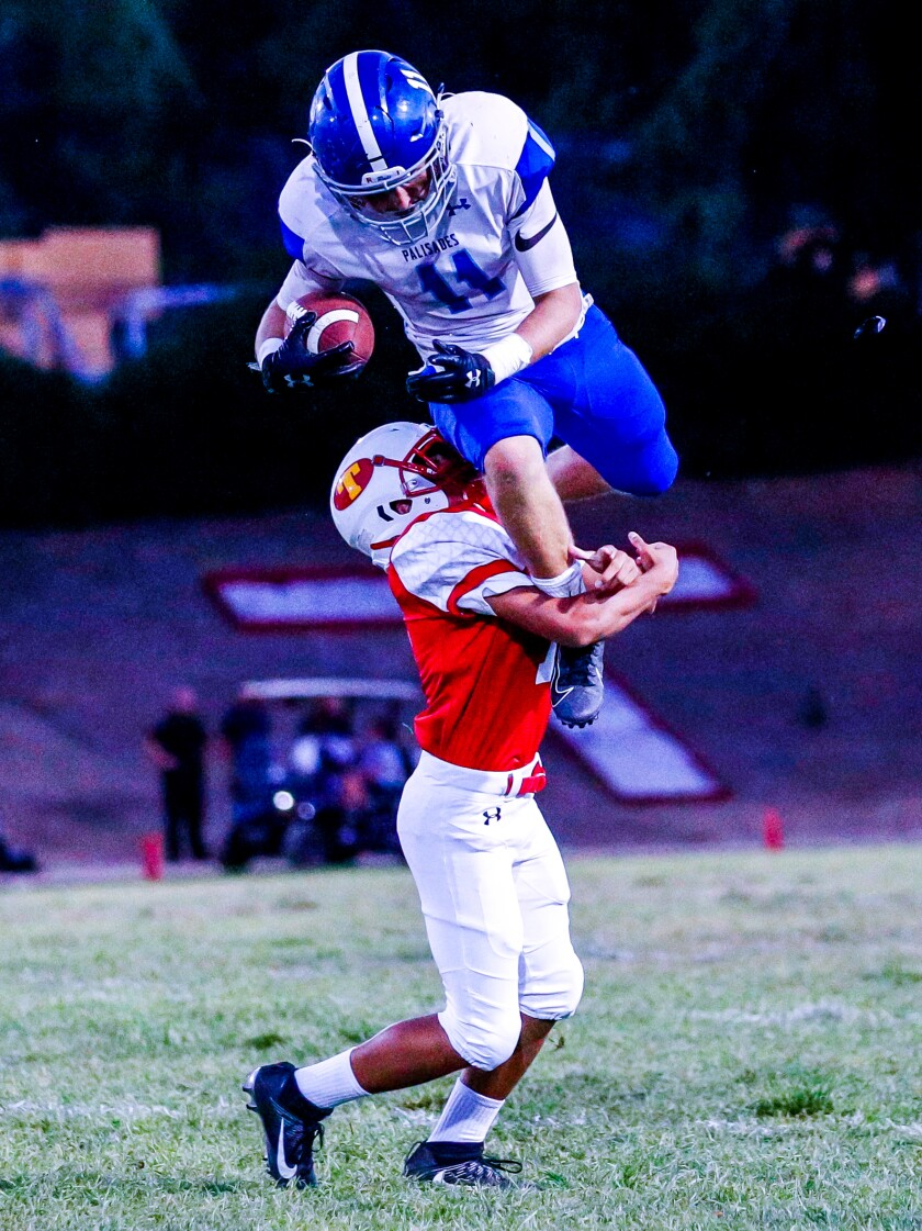 Max Palees of Palisades leaps over a Taft defender. Palisades plays Venice on Friday.
