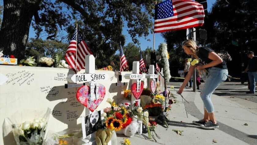 A resident of Newbury Park places flowers at a makeshift memorial for the victims of the Nov. 7, 2018, mass shooting in Thousand Oaks.