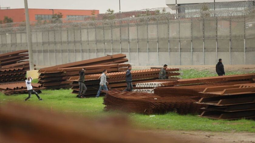 Men surrender to U.S. Border Patrol agents after jumping a border fence in Tijuana on Thursday.