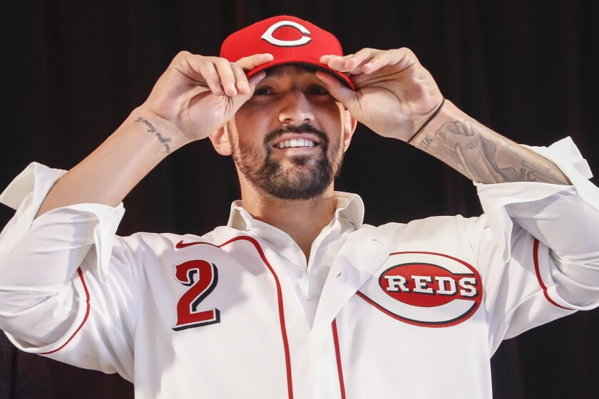 The Reds' Nick Castellanos puts on his cap during a news conference, Tuesday, Jan. 28, 2020, in Cincinnati. Castellanos signed a $64 million, four-year deal with the baseball club.