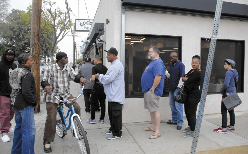 """Patrons line up outside Locol on Tuesday, its second day of business. The """"energy of Watts, this specific neighborhood, is on the block,"""" chef Roy Choi says."""