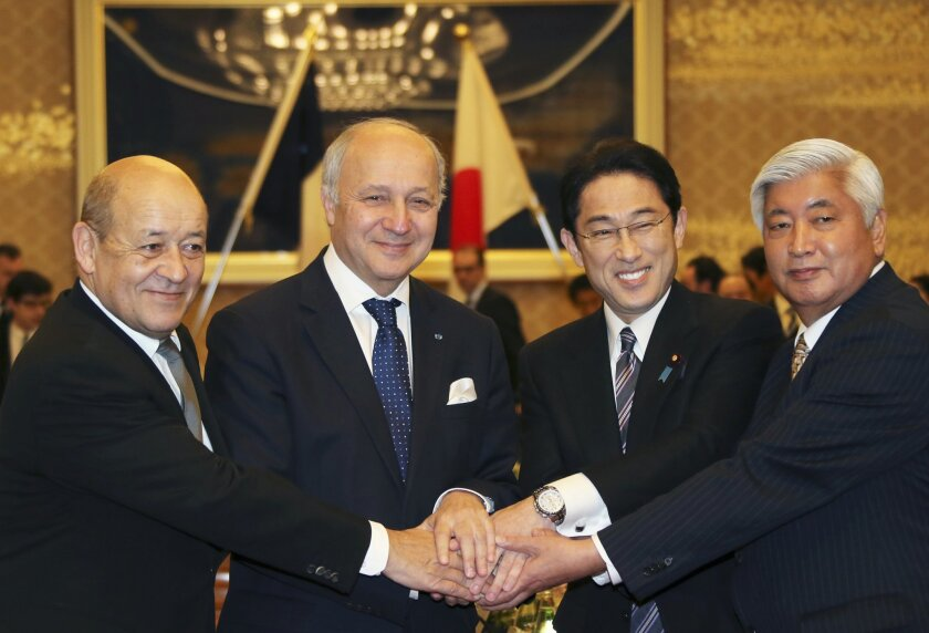 French Defense Minister Jean-Yves Le Drian, left, and French Foreign Minister Laurent Fabius, second left, join hands with Japanese Foreign Minister Fumio Kishida, seond right, and Japanese Defense Minister Gen Nakatani during a Japan-France two-plus-two meeting in Tokyo, Friday, March 13, 2015. Japan and France signed an arms transfer agreement Friday, paving the way for developing drones and other unmanned equipment together as Japan seeks to play a greater military role internationally. (AP Photo/Koji Sasahara,pool)