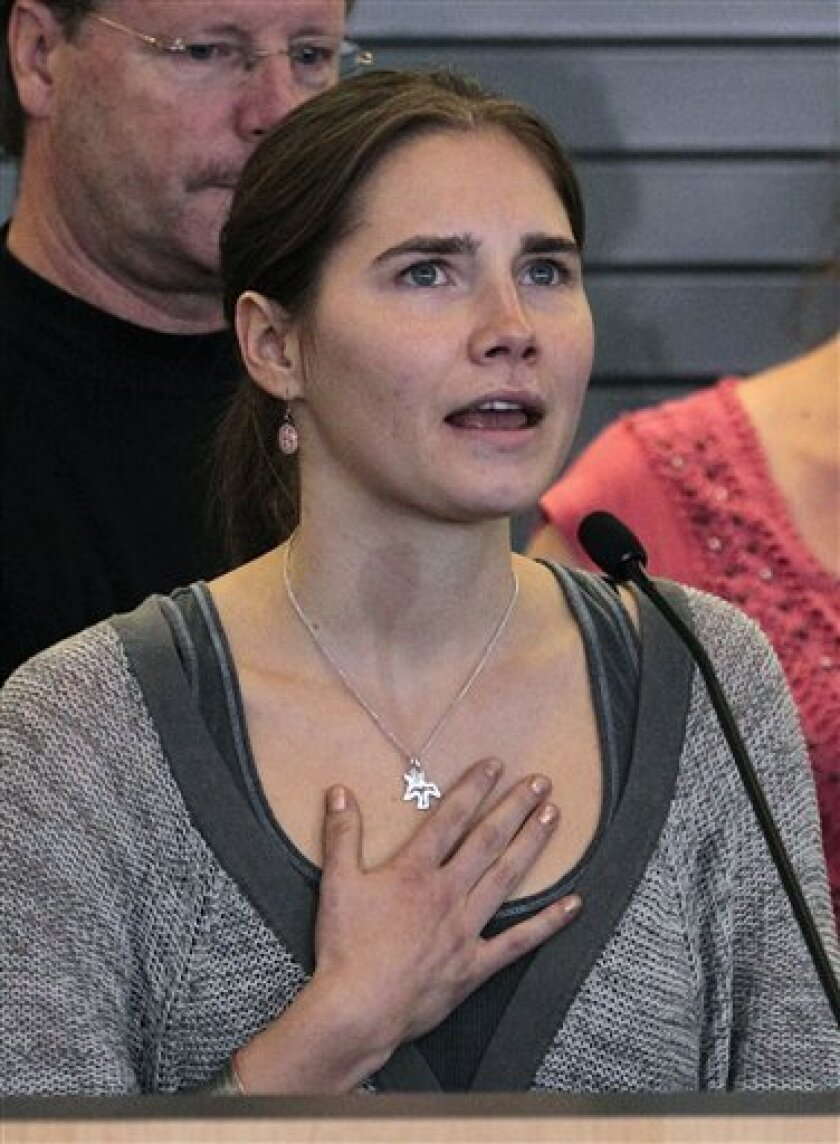 FILE - In this Oct. 4, 2011 file photo, Amanda Knox, standing in front of her father, Curt Knox, and other supporters, speaks at a news conference shortly after her arrival at Seattle-Tacoma International Airport in Seattle. Knox was freed on October 3 after an Italian appeals court acquitted her on murder charges after four years in prison. Curt Knox says Amanda would like to go back to her university and finish her degree, but that he worries about what the time in prison has done to his 24-year-old daughter. (AP Photo/Elaine Thompson, File)