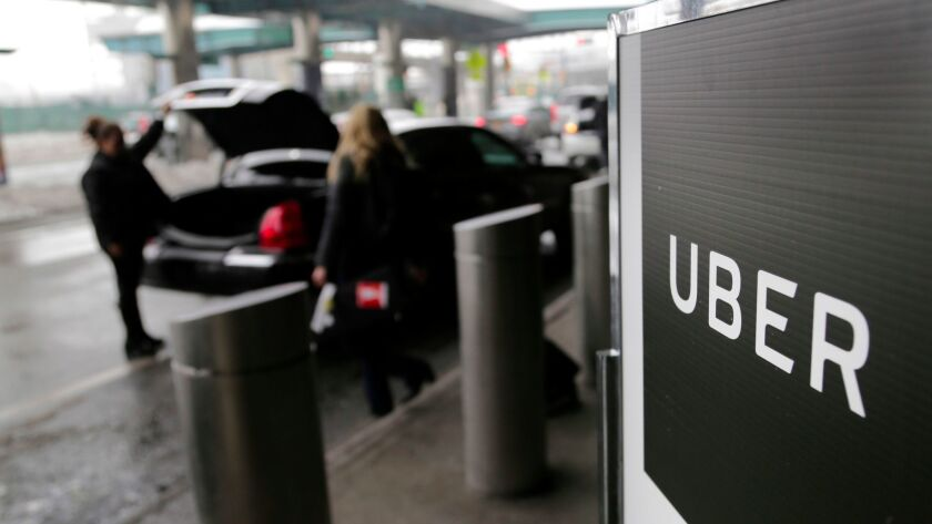 FILE - In this March 15, 2017, file photo, a sign marks a pick-up point for the Uber car service at