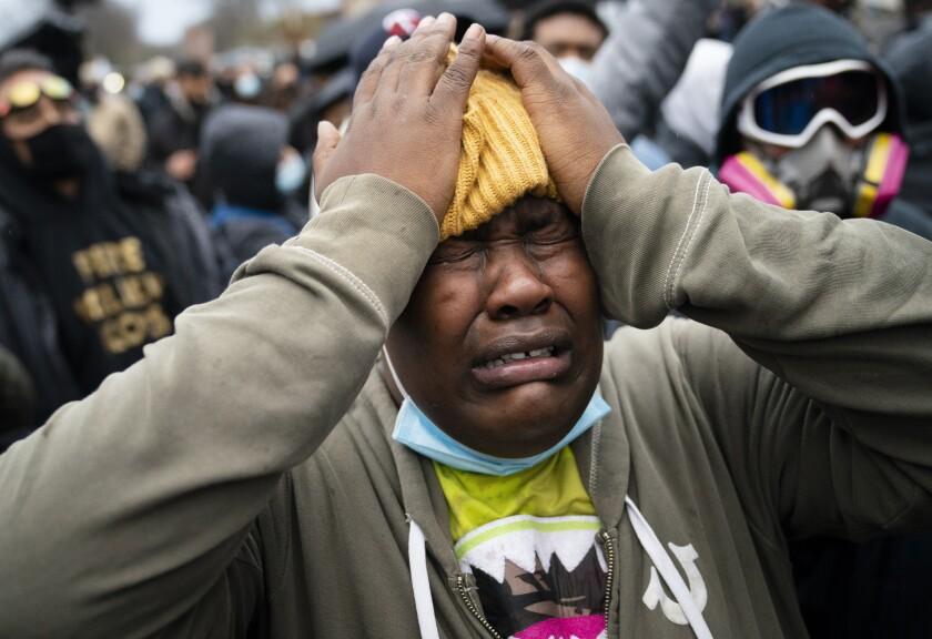 A demonstrator reacts during a standoff with police along a perimeter fence during a protest decrying the shooting death of Daunte Wright, outside the Brooklyn Center Police Department, Wednesday, April 14, 2021, in Brooklyn Center, Minn. (AP Photo/John Minchillo)