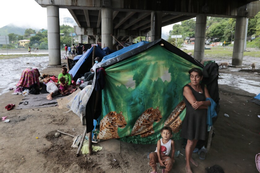 Hurricane victims take refuge under a bridge in San Pedro Sula, Honduras, Saturday, Nov. 21, 2020. Shelters for people whose homes were flooded or damaged by hurricanes Eta and Iota in Honduras are now so crowded that thousands of victims have taken refuge under highway overpasses or bridges. The Red Cross estimates that about 4.2 million people were affected by the back-to-back hurricanes in November in Honduras, Nicaragua and Guatemala. (AP Photo/Delmer Martinez)