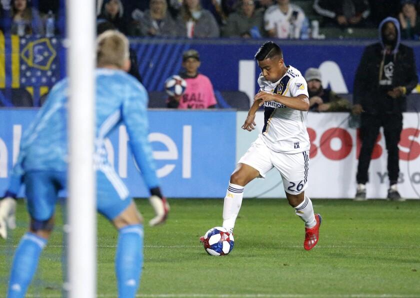 Galaxy forward Efraín Álvarez prepares to take a shot against Sporting Kansas City goalkeeper Adrian Zendejas in 2019.
