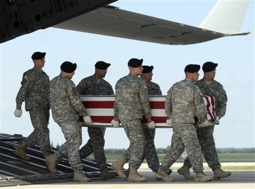 An Army carry team carries a transfer case containing the remains of Spc. Issac L. Johnson Wednesday July 8, 2009 at Dover Air Force Base, Del. According to the Department of Defense, Johnson, of Columbus, Ga., died while supporting Operation Enduring Freedom. (AP Photo/Steve Ruark)
