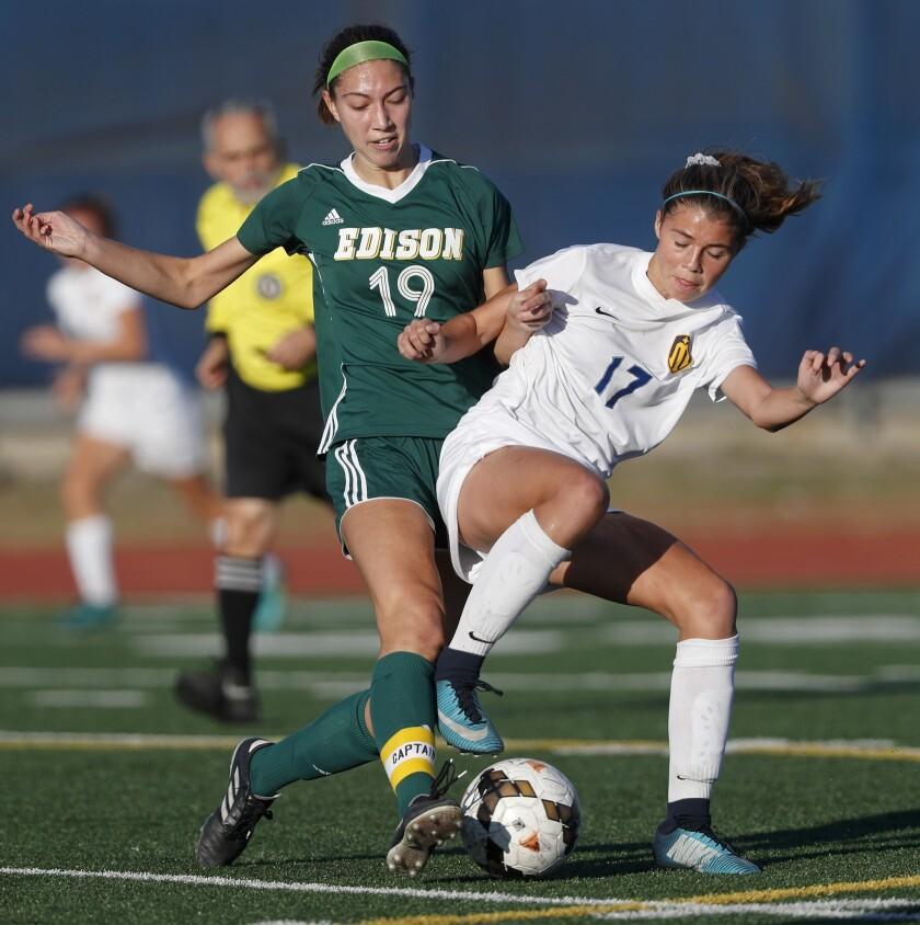 Marina High's Kaitlyn Paculba (17) battles Edison's Kayla Herbert (19) for the ball during the first