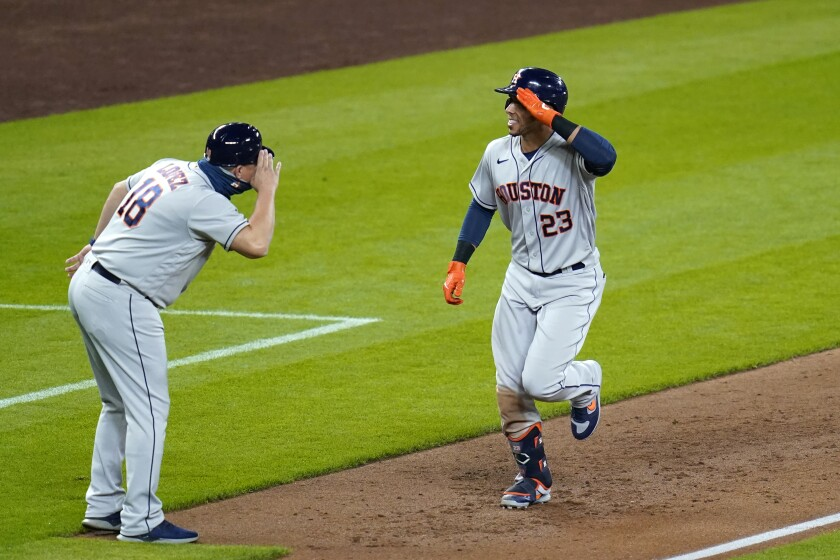 Houston Astros' Michael Brantley (23) shares a salute with third base coach Omar Lopez as Brantley heads toward home after hitting a solo home run against the Seattle Mariners during the sixth inning of a baseball game Tuesday, Sept. 22, 2020, in Seattle. (AP Photo/Elaine Thompson)