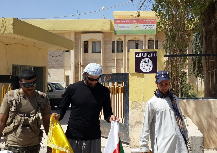 Islamic State militants and tribal fighters take down Kurdish flags from the headquarters of the Kurdistan Democratic Party in the Christian village of Bartella, Iraq, on Aug. 7.