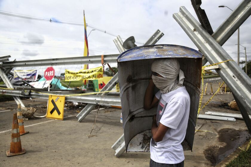 A protester stands at a road block set up during anti-government protests in Cali, Colombia, Monday, May 10, 2021. Colombians have protested across the country against a government they feel has long ignored their needs, allowed corruption to run rampant and is so out of touch that it proposed tax increases during the coronavirus pandemic. (AP Photo/Andres Gonzalez)