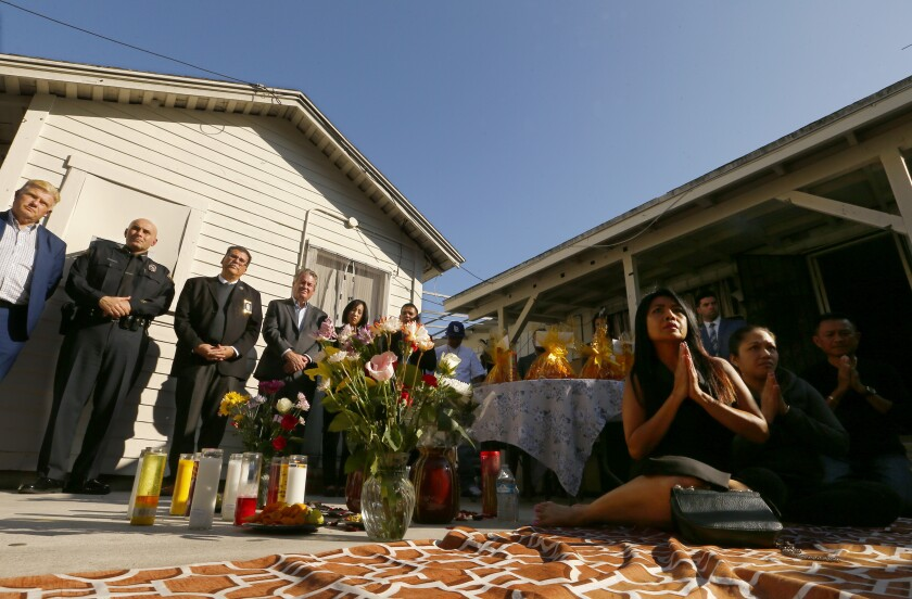 Family and friends of shooting victims are joined by government officials on Nov. 5 during a traditional Buddhist memorial ceremony in the backyard of a home in Long Beach where three people were killed Halloween night.
