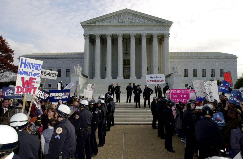 Police officers in riot gear separate the George W. Bush supporters from the Al Gore supporters in front of the Supreme Court on Dec. 1, 2000.