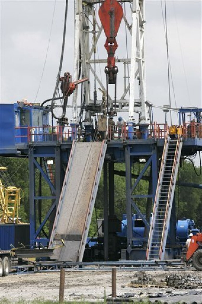 In this May 2, 2007 file photo, workers are shown at a drilling site within the Fort Worth, Texas, city limits. Over the next 20 years or so, oil and natural gas will lose top ranking as the world's most affordable energy sources, according to a survey of energy executives released Wednesday, Dec. 10, 2008. (AP Photo/Donna McWilliam, File)