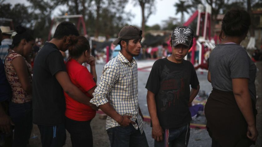Central American migrants in a caravan stand in line to start their documentation with a Mexican immigration official in Matias Romero, Oaxaca state, Mexico on April 2.