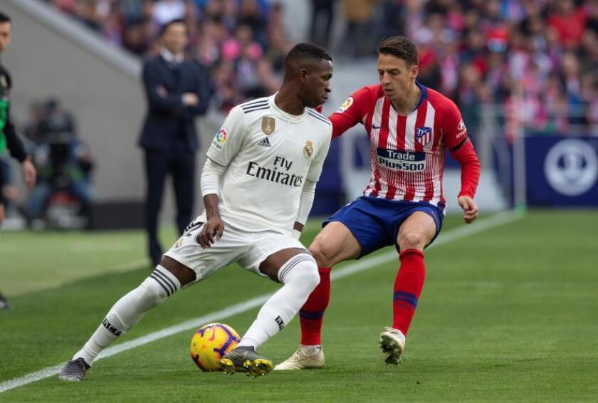 El delantero brasileño del Real Madrid Vinicius Júnior (i) y el defensa colombiano del Atlético de Madrid Santiago Arias durante el partido de la vigésimo tercera jornada de Liga que disputaron en el estadio Wanda Metropolitano de Madrid. EFE