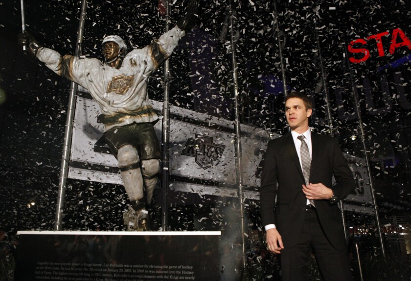 Kings great Luc Robitaille steps in front of his newly unveiled bronze statue outside Staples Center at Star Plaza during a ceremony on Saturday night.
