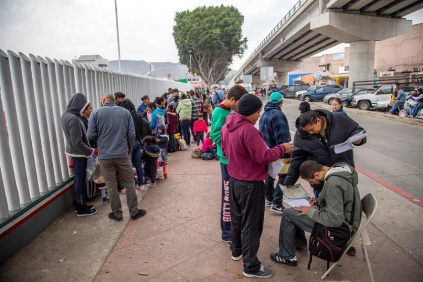 Un grupo de migrantes venezolanos, guatemaltecos, hondureños y mexicanos esperan para iniciar la solicitud de visa humanitaria afuera de la oficina fronteriza estadounidense de El Chaparral, en la frontera de la ciudad de Tijuana, en el estado de Baja California, con Estados Unidos. EFE/Archivo