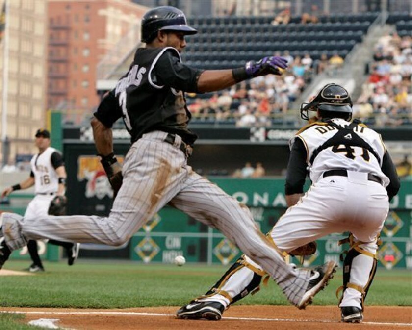 Pittsburgh Pirates catcher Ryan Doumit, right, waits for the late throw as Colorado Rockies' Willy Taveras scores on a first-inning single by Brad Hawpe in a baseball game in Pittsburgh on Tuesday, July 29, 2008. (AP Photo/Gene J. Puskar)