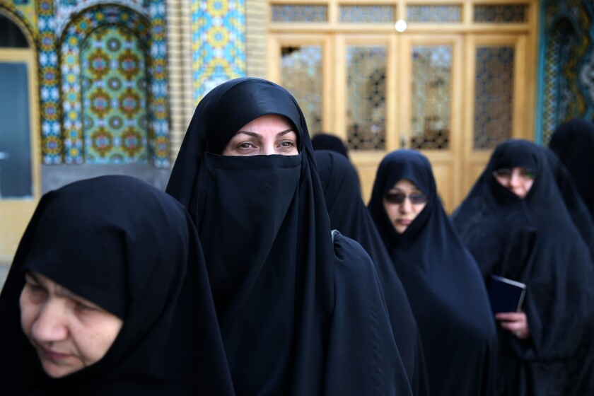 Iranian women stand in line at a polling station during the parliamentary elections in Qom, south of Tehran, on Feb. 26, 2016.