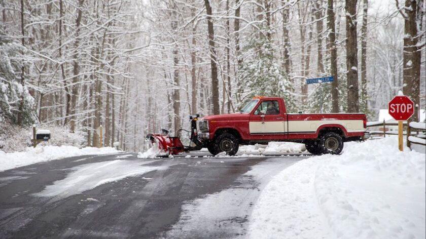 A snowplow operator clears a private road Sunday after a winter storm dumped a blanket of snow in Fairfax Station, Va.