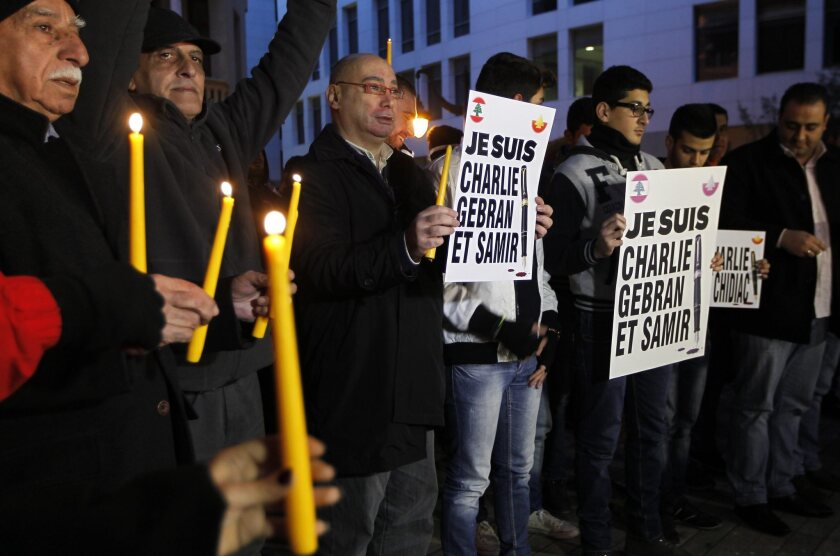 "Lebanese protesters hold candles and placards reading in French ""I am Charlie, Gebran and Samir' during a gathering in solidarity with victims of the Charlie Hebdo attack."