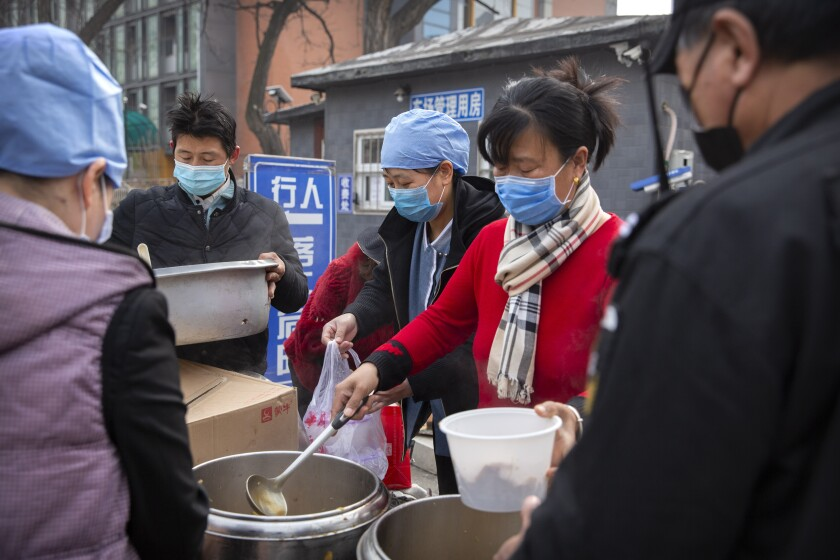 Masked workers serve lunch to masked customers outside an office building in Beijing on Friday.