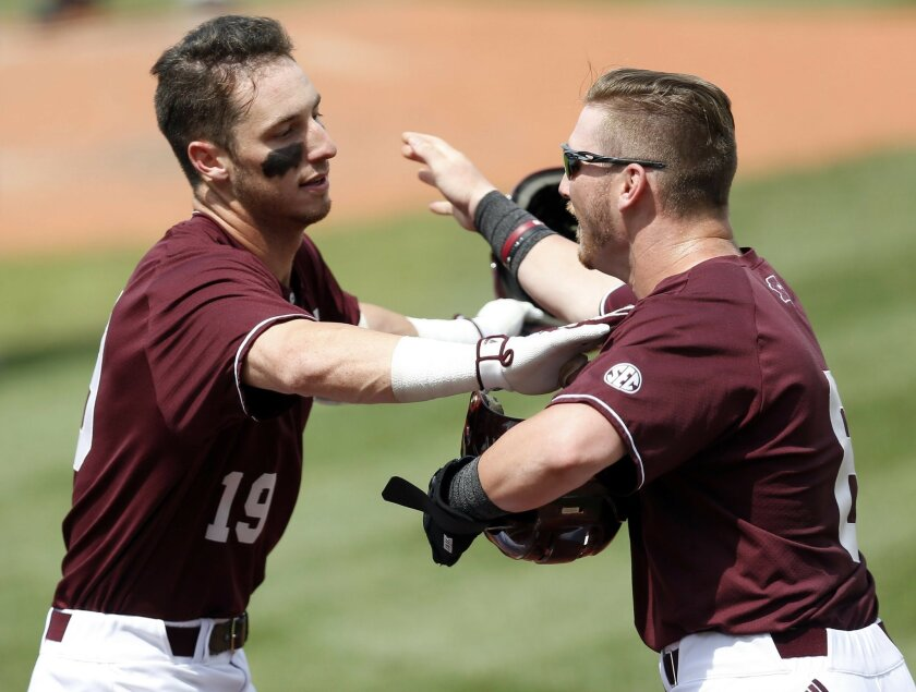 Mississippi State's Brent Rooker (19) left, is congratulated by teammate Gavin Collins (8), following Rooker's second home run against Southeast Missouri State during their NCAA Regional Baseball Tournament game at Dudy Noble Field in Starkville, Miss., Friday, June 3, 2016. (AP Photo/Rogelio V. So