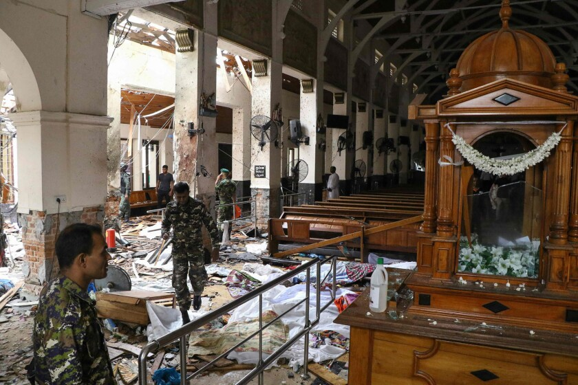 Sri Lankan security personnel pass bodies covered with blankets amid blast debris at St. Anthony's Shrine.