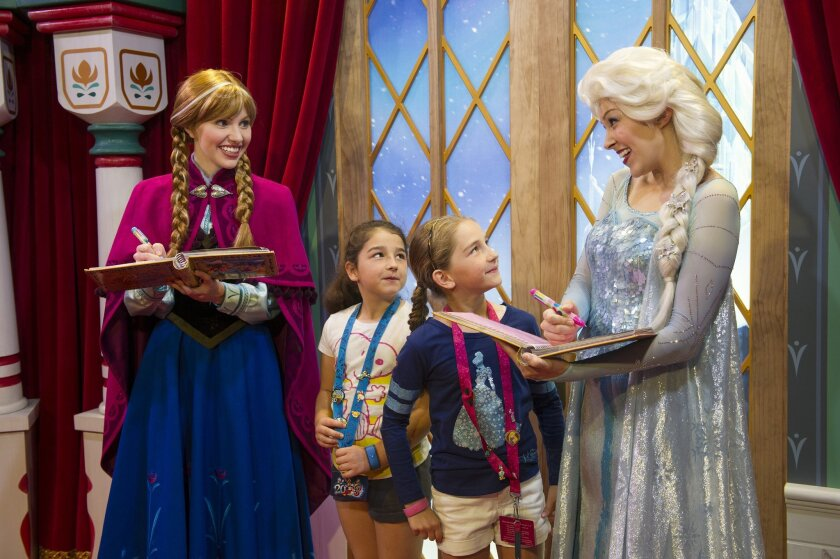 """FILE - This Nov. 15, 2013 file photo released by Disney shows unidentified Epcot guests meeting Disney characters Anna, left, and her sister Elsa from the animated film """"Frozen"""" at the Norway Pavilion at Walt Disney World Resort in Lake Buena Vista, Fla. The meet-and-greets began in November, 2013, at the Norway Pavilion at Disney's Epcot park, but they are now held at Princess Fairytale Hall in the Magic Kingdom. Wait times to meet the sisters stretches for hours and reservations are snapped up as soon as they become available, part of a frenzy for all things """"Frozen."""" (AP Photo/Disney, Gene Duncan)"""