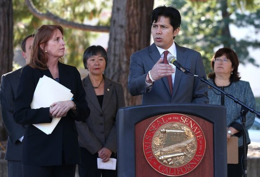California Sen. Noreen Evans (D-Santa Rosa), left, looks on as Sen. Kevin de Leon (D-Los Angeles) speaks during a news conference in Santa Rosa where they proposed that mock guns be produced in bright colors.