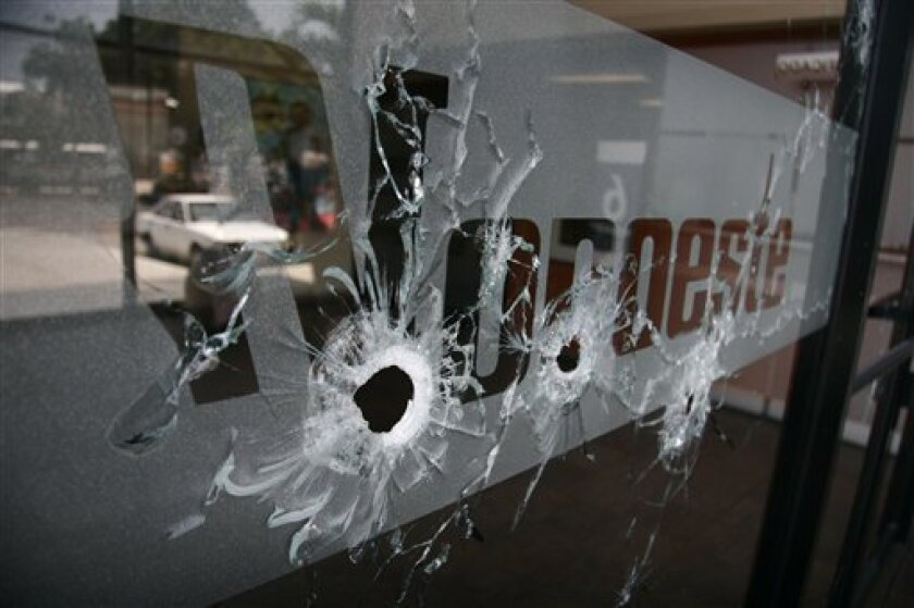 """The entrance of El Noroeste newspaper is covered with bullet holes after unidentified gunmen opened fire on the newspaper's offices in the Pacific resort city of Mazatlan, Mexico, Wednesday Sept. 1, 2010. According to el Noroeste, the attack came hours after anonymous calls were made to the newspaper by a group that identified itself as """"La Linea,"""" or The Line, demanding that the daily publish stories related to the illegal activities of the Sinaloa drug cartel. (AP photo/Christiann Davis)"""