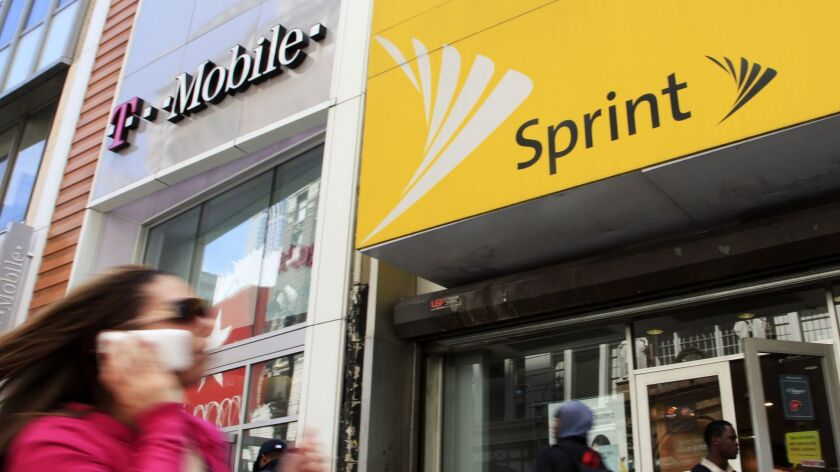 A woman using a cell phone walks past T-Mobile and Sprint stores in New York City on April 27, 2010.