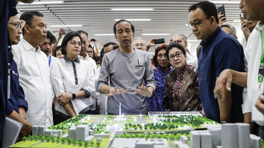Indonesian President Joko Widodo, center, has made infrastructure building a priority of his administration. Here he is shown inspecting a model of Jakarta's new mass transit line in March 2019.